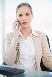 Peaceful blonde businesswoman having a phone call posing