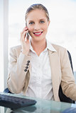 Cheerful blonde businesswoman having a phone call posing