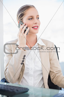 Smiling blonde businesswoman having a phone call posing