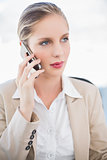 Pensive blonde businesswoman having a phone call posing
