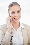Smiling blonde businesswoman on the phone posing
