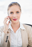Peaceful blonde businesswoman on the phone posing