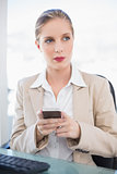 Peaceful blonde businesswoman text messaging