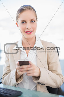 Smiling blonde businesswoman text messaging