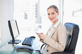 Cheerful blonde businesswoman text messaging
