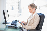 Focused blonde businesswoman using tablet