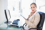 Thoughtful blonde businesswoman using tablet