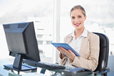 Cheerful blonde businesswoman using tablet