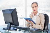 Pensive blonde businesswoman using tablet