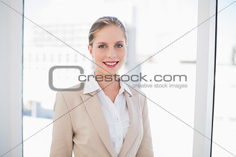 Smiling blonde businesswoman standing
