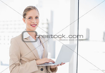 Smiling blonde businesswoman using laptop
