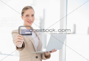 Smiling blonde businesswoman showing credit card holding laptop
