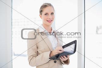 Smiling blonde businesswoman writing on datebook