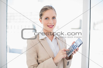 Smiling blonde businesswoman using calculator