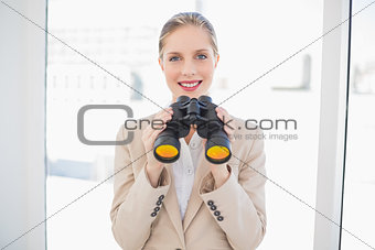 Smiling blonde businesswoman holding binoculars