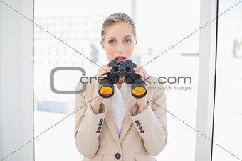 Astonished blonde businesswoman holding binoculars