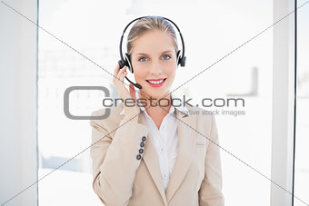 Smiling blonde call centre agent standing