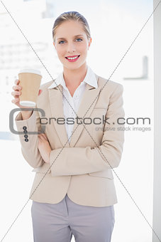 Smiling blonde businesswoman holding coffee
