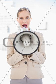 Blonde businesswoman shouting in megaphone