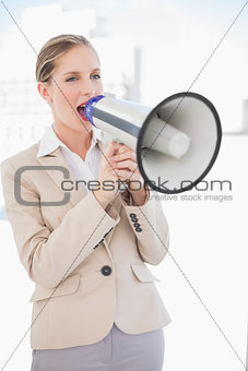 Angry blonde businesswoman screaming in megaphone