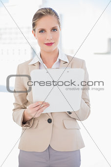 Smiling blonde businesswoman holding clipboard