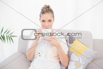 Charming fresh model drinking coffee sitting on sofa