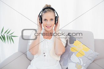 Charming fresh model listening to music sitting on sofa