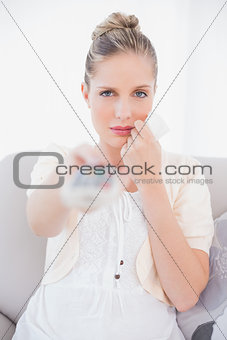Anxious fresh model changing tv channel sitting on sofa
