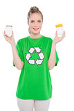 Smiling environmental activist wearing recycling tshirt holding jars