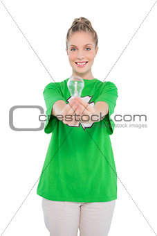 Smiling activist wearing recycling tshirt holding light bulb