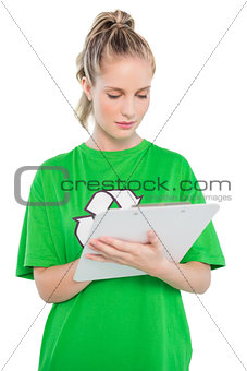 Focused blonde activist writing on clipboard