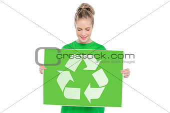 Content blonde environmental activist holding recycling sign
