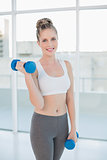 Smiling athletic blonde exercising with dumbbells