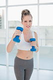 Competitive sporty blonde exercising with dumbbells