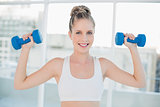 Smiling sporty blonde lifting dumbbells