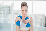 Smiling sporty blonde working out with dumbbells