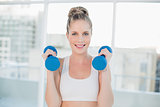 Cheerful sporty blonde working out with dumbbells