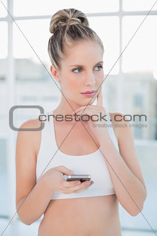 Thoughtful sporty blonde text messaging