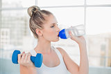 Peaceful sporty blonde drinking water while lifting dumbbell