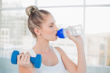 Relaxed sporty blonde drinking water while lifting dumbbell