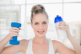 Smiling sporty blonde holding flask and dumbbell