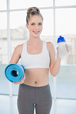 Smiling sporty blonde holding flask and exercise mat