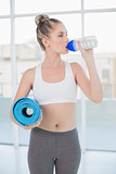 Sporty blonde drinking water holding exercise mat