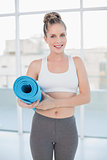 Smiling sporty blonde holding balled up exercise mat