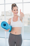 Sporty blonde holding balled up exercise mat giving thumb up