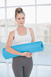 Peaceful sporty blonde holding balled up exercise mat