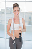 Smiling sporty blonde holding skipping rope around neck