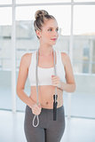 Pensive sporty blonde holding skipping rope around neck