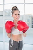 Angry sporty blonde wearing red boxing gloves