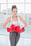 Furious sporty blonde wearing red boxing gloves